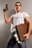 Contemporery business. Man with gun and case of dollars Stock Photos