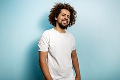 Contended smile on the face of a curly-headed brunet man wearing white T-shirt. A person with a look of pleasure. stock image