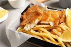 Conteneur avec les poissons et les pommes chips traditionnels britanniques images libres de droits