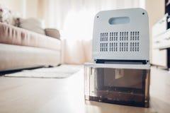 Conteneur changeant de l'eau de déshumidificateur à la maison Humidité en appartement Technologie moderne images stock