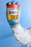 Conteneur d'urine avec le bar de code à l'arrière-plan bleu Images stock