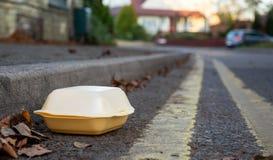 Conteneur de nourriture jeté dans la gouttière par le côté de la route image libre de droits