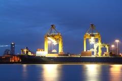 Conteneurs chargeant au port de commerce de mer au crépuscule Image stock