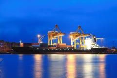 Conteneurs chargeant au port de commerce de mer au crépuscule Images libres de droits