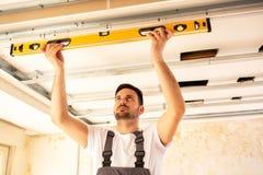 Contenga al trabajador de la renovación que comprueba la alineación de un techo imagen de archivo libre de regalías