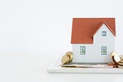 """Contenga el †del concepto de la propiedad """"una casa modelo en una pila de monedas Fotografía de archivo"""