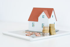 """Contenga el †del concepto de la propiedad """"una casa modelo en una pila de monedas Foto de archivo libre de regalías"""