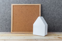Contenga el concepto con cartulina de la forma de la casa en piso y gre de madera Imagenes de archivo