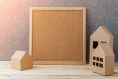 Contenga el concepto con cartulina de la forma de la casa en piso y gre de madera Fotografía de archivo libre de regalías