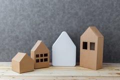 Contenga el concepto con cartulina de la forma de la casa en piso y gre de madera Fotos de archivo libres de regalías