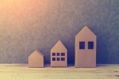 Contenga el concepto con cartulina de la forma de la casa en piso y gre de madera Fotos de archivo