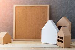Contenga el concepto con cartulina de la forma de la casa en piso y gre de madera Foto de archivo libre de regalías