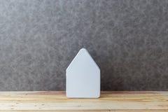 Contenga el concepto con cartulina de la forma de la casa en piso y gre de madera Foto de archivo