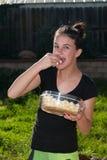 Contenido de la chica joven mientras que snacking en las palomitas Foto de archivo