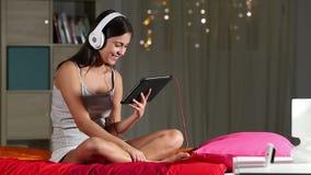 Contenido de observación adolescente feliz de la tableta que se sienta en una cama almacen de metraje de vídeo