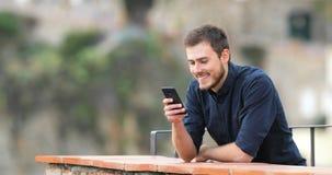 Contenido de observación del teléfono del hombre feliz en un balcón metrajes