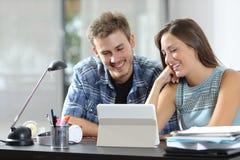 Contenido de observación de la tableta de los pares felices en un escritorio en casa fotos de archivo libres de regalías