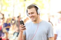 Contenido de observación y que escucha del individuo medios en el teléfono Foto de archivo