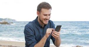 Contenido del teléfono de la ojeada del hombre en la playa