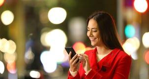Contenido del teléfono de la ojeada de la mujer en una noche del invierno almacen de metraje de vídeo