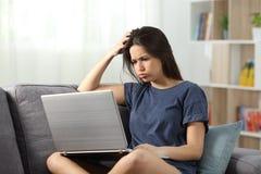 Contenido en línea de la lectura adolescente confusa en casa Imagen de archivo