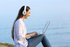 Contenido en línea de la mujer de observación y que escucha al aire libre Fotografía de archivo libre de regalías