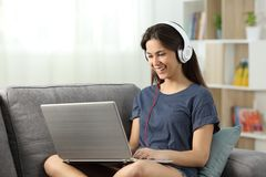 Contenido en línea de observación y que escucha adolescente feliz Imagenes de archivo