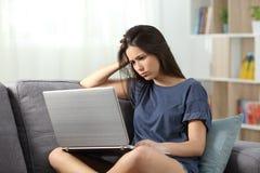 Contenido en línea frustrado de la lectura adolescente en casa Foto de archivo