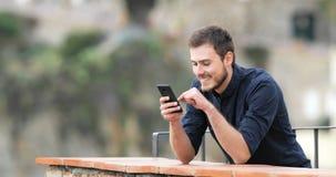 Contenido feliz del teléfono de la ojeada del hombre en un balcón almacen de metraje de vídeo