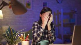 Contenido impactante de observación de la chica joven en el ordenador portátil que se sienta en su apartamento moderno almacen de metraje de vídeo