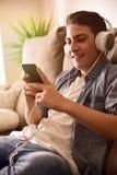 Contenido multimedia de observación del adolescente con los auriculares en el cl del sofá Imagen de archivo libre de regalías