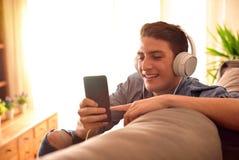 Contenido multimedia de observación del adolescente que se inclina en la parte de atrás de couc Fotos de archivo