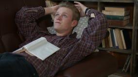 Contenido sanalyzing masculino contemplativo del libro almacen de metraje de vídeo