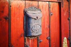 Contenitore d'annata nero di posta sulla parete rossa Fotografia Stock Libera da Diritti