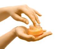 Contenitore della stretta della mano con crema Immagini Stock