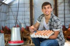 Contenitore della tenuta dell'agricoltore dell'uomo con le uova fresche Fotografia Stock