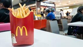 Contenitore delle patate fritte in pacchetto rosso sulla tavola bianca al caffè del ` s di McDonald fotografie stock
