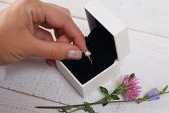 Contenitore di anello di fidanzamento in mani della sposa Primo piano delle palme della donna che tengono gioielli Amore, nozze,  Immagini Stock