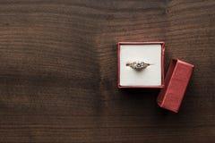 Contenitore di anello in rosso sulla tavola Fotografia Stock Libera da Diritti