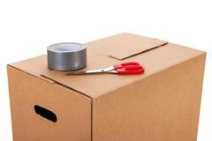 Contenitore di cartone con le forbici e nastro adesivo Fotografie Stock Libere da Diritti