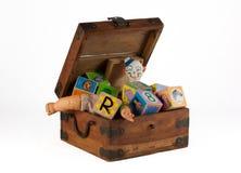 Contenitore di giocattolo dell'annata con la bambola, il pagliaccio ed i blocchi Fotografia Stock