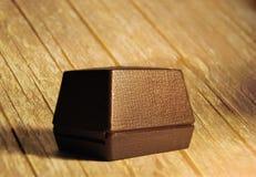 Contenitore di gioielli marrone chiuso su una vecchia tavola di legno Immagine Stock
