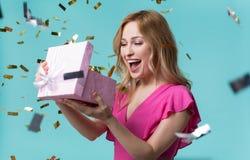 Contenitore di regalo allegro di apertura della ragazza con interesse Fotografia Stock Libera da Diritti