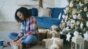 Contenitore di regalo attraente dell'imballaggio della ragazza della corsa mista vicino all'albero di Natale a casa Immagini Stock Libere da Diritti