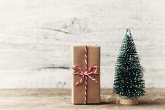 Contenitore di regalo avvolto in carta kraft e poco albero di abete decorativo su fondo rustico di legno Concetto anno di nuovo e fotografie stock libere da diritti
