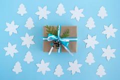 Contenitore di regalo avvolto della carta del mestiere, nastri blu e bianchi e rami e pinecone decorati dell'abete sui precedenti Fotografia Stock