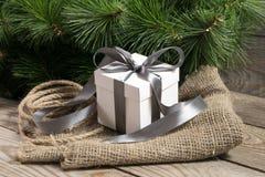 Contenitore di regalo bianco con i nastri, il ramo di albero di cristmas e la corda grigi Fotografie Stock Libere da Diritti
