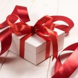 Contenitore di regalo bianco con i nastri rossi isolati sul backgro di legno bianco Fotografia Stock Libera da Diritti