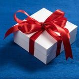 Contenitore di regalo bianco con il nastro rosso su fondo blu Fotografia Stock Libera da Diritti
