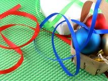 Contenitore di regalo bianco con l'arco del nastro e la merce nel carrello verdi delle palle di natale Fotografia Stock